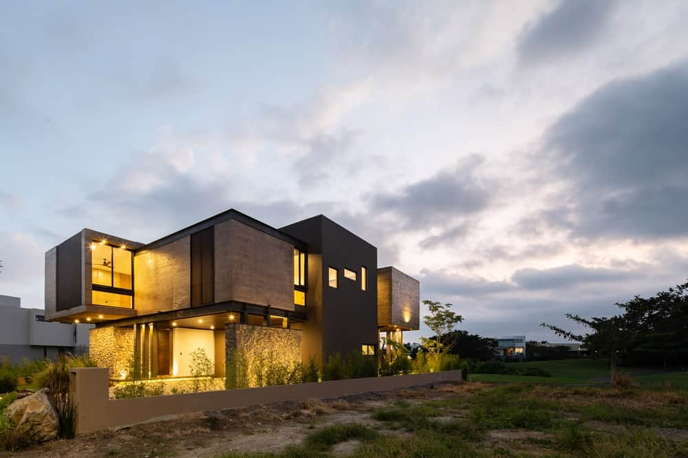The earthy structures of the house are complemented by the warm lighting that matches the indoor with the outdoor.