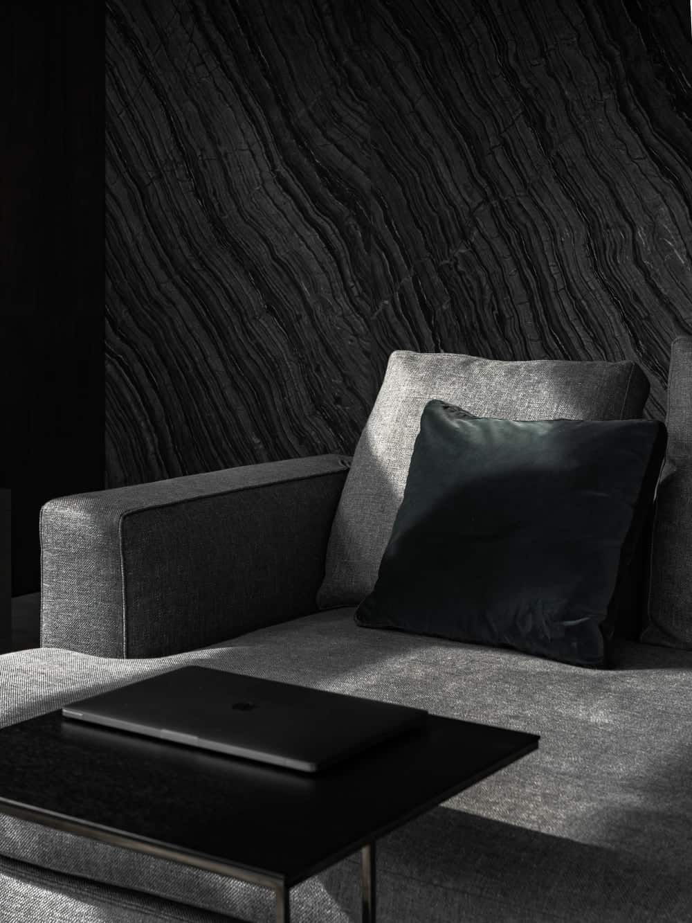 The edge of the sofa is paired with a modern black side table that serves as a desk for the laptop.