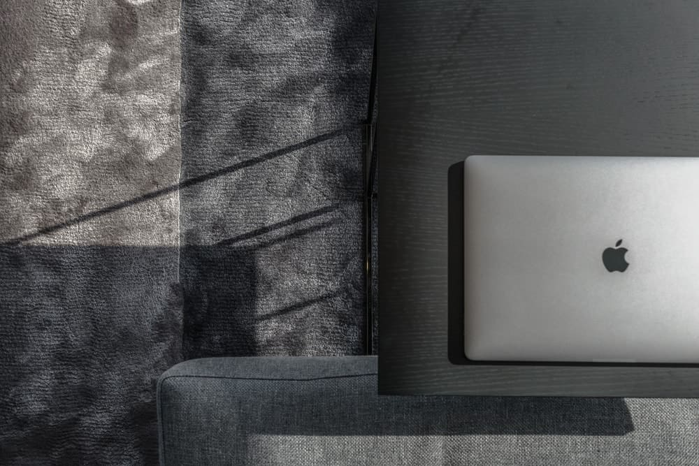 This is a close look at the modern side table, the gray sofa and the gray area rug underneath showing different shades of gray.