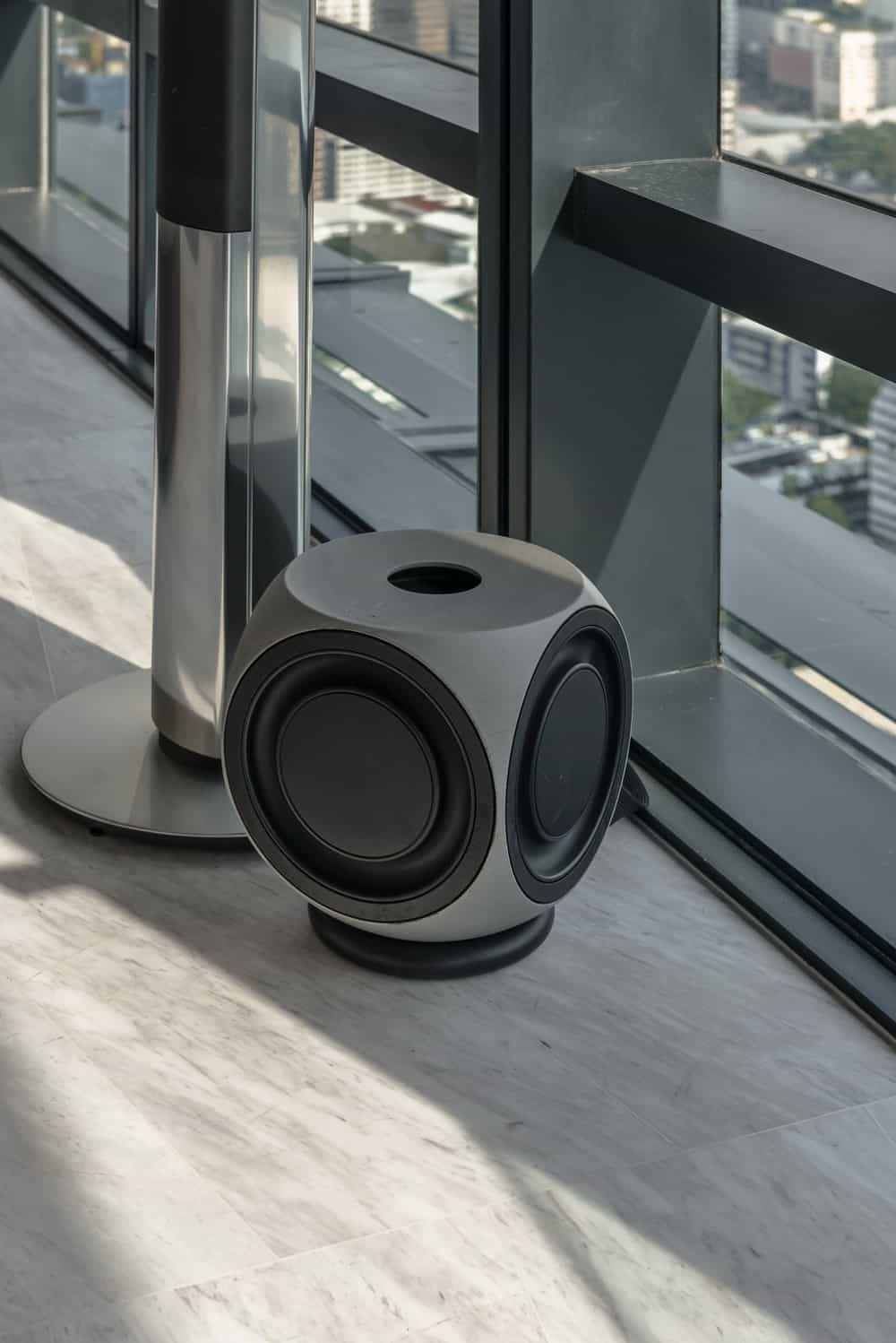 On one corner of the bedroom is this modern stereo speaker by the window.