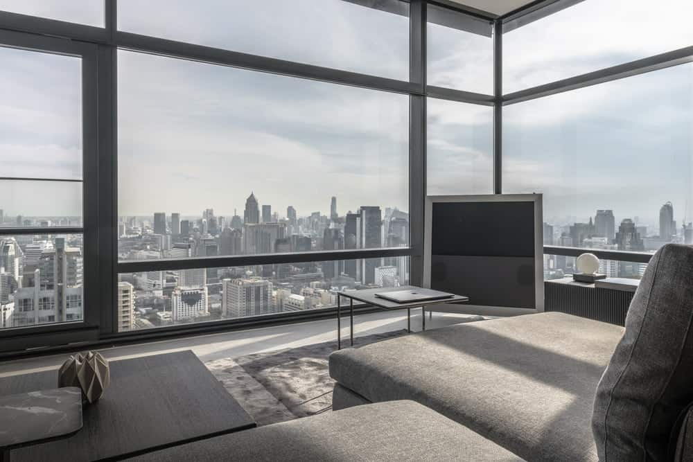 The highlight of the living room is the city skyline view presented by the glass walls.