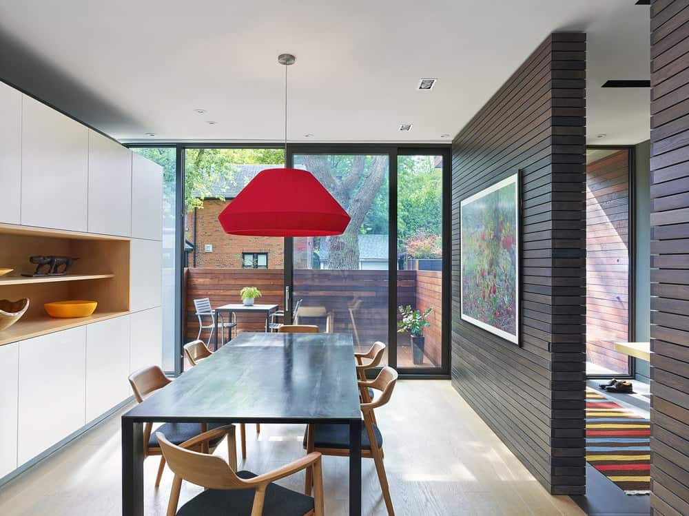 This view of the dining room showcases the red dome pendant light over the kitchen table that matches the dark wall on the side.