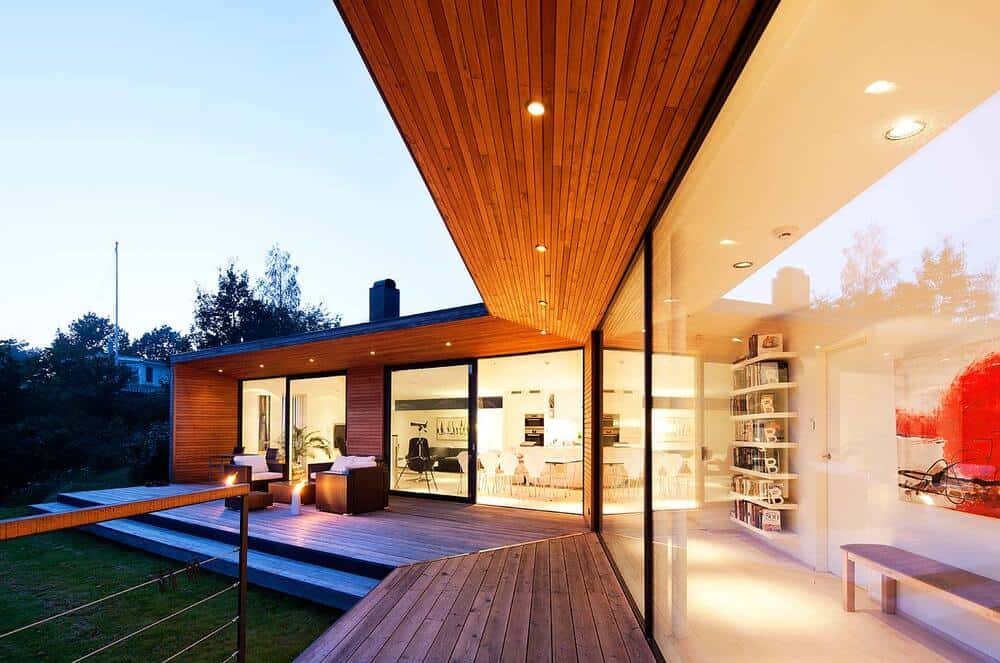 The recessed lights of the wooden ceiling augment the spill-over light that comes from the glass walls.