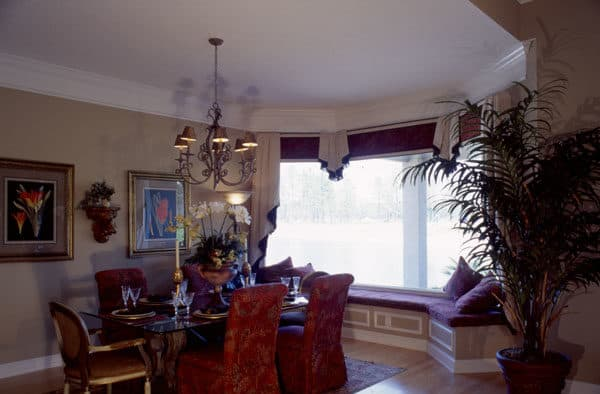 The dining area offers a glass top dining table, skirted chairs, an ornate chandelier, and a window seat.