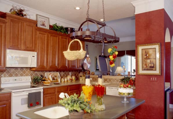 Kitchen with natural wood cabinetry, white appliances, and an oval pot rack hanging above the center island.