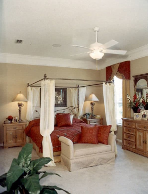 Primary bedroom with a wooden dresser, matching nightstands, and a canopy bed with a Cleopatra bed at its end.