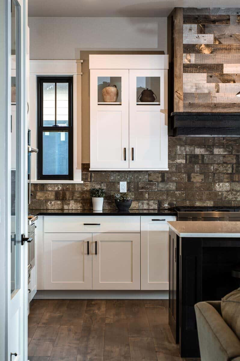 A closer look at the white cabinets that are contrasted with rustic subway tile backsplash.