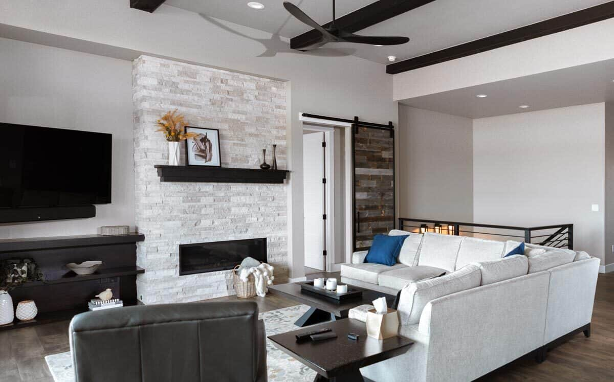 Living room with a modern fireplace, a wall-mounted TV, dark wood cabinets, L-shaped sectional, and a leather armchair.