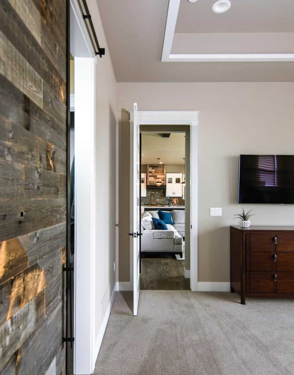 Wall-mounted TV fixed above the wooden dresser completes the primary bedroom.