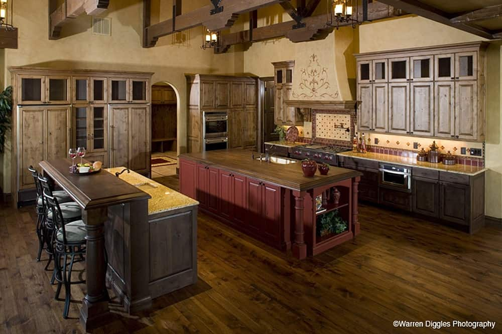 Kitchen with two islands and light wood cabinetry that blends in with the hardwood flooring.