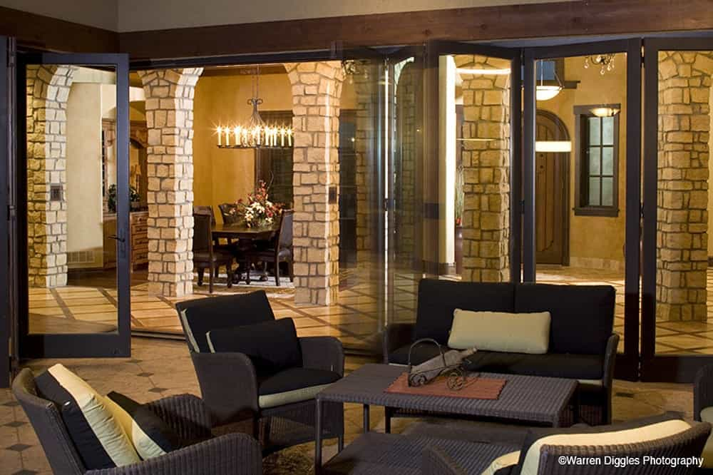 Folding glass doors open to the covered patio that's filled with wicker seats and a matching table.