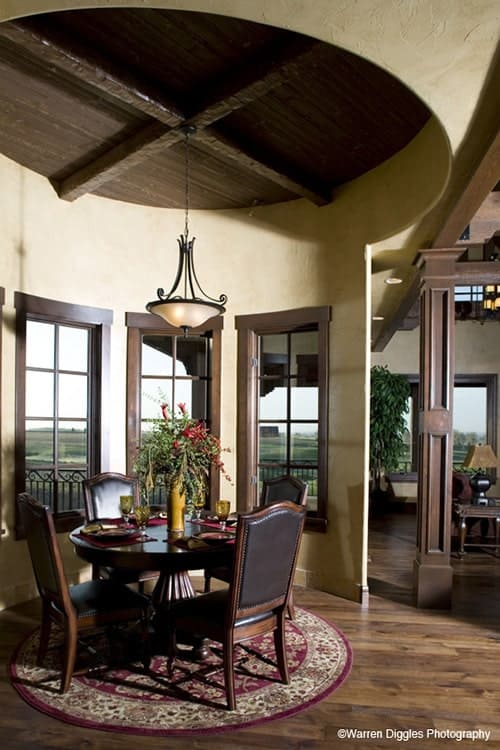 Breakfast nook with a glass dome pendant, a round dining set, and a red bordered rug.