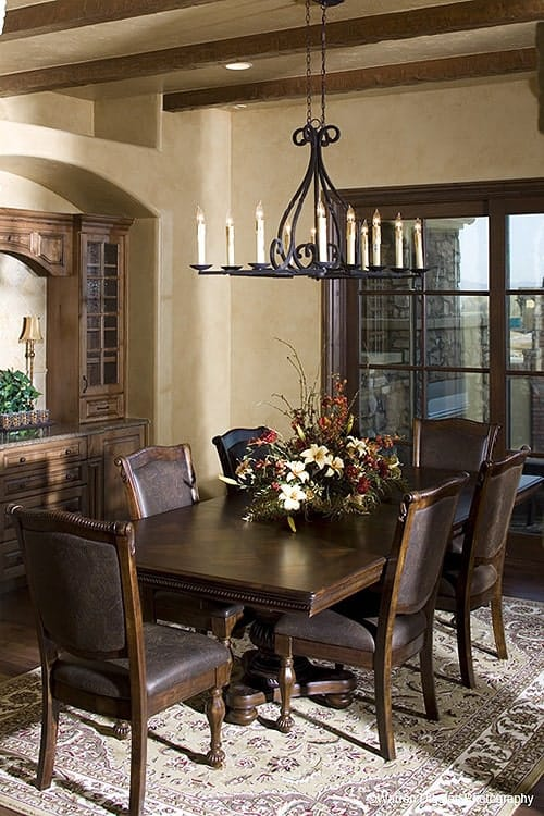The formal dining room offers a candle chandelier, a classic area rug, leather upholstered chairs, and a wooden dining table topped with decorative flowers.