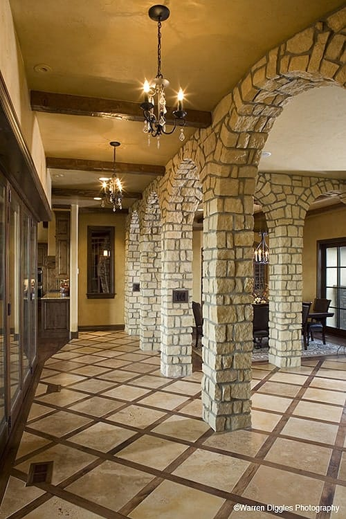 Hallway with brick archways, beamed ceiling, and wrought iron chandeliers.