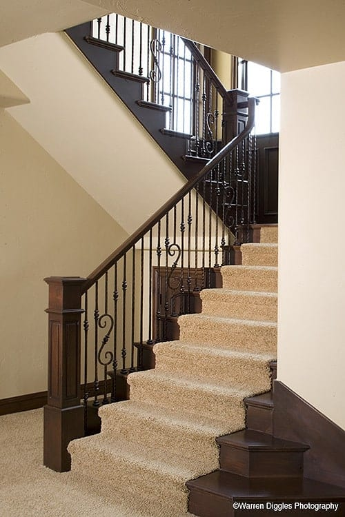Traditional staircase with ornate railings and dark wood steps covered in a beige carpet.