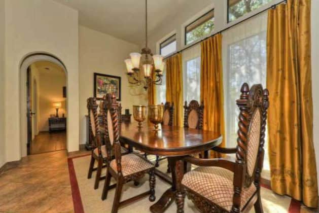 The dining room has an iron chandelier, oval dining table, cushioned chairs, and a bordered area rug.
