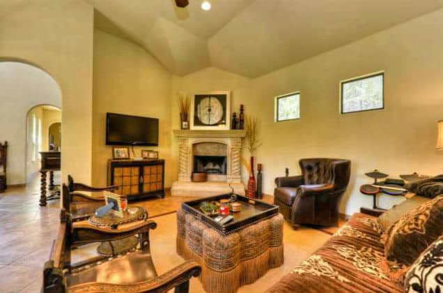Living room with a corner fireplace, a wall-mounted TV, cozy chairs, and a classy ottoman topped with a wooden tray.