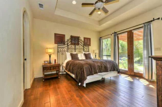The primary bedroom has a tray ceiling, wide plank flooring, and a comfy bed with an ornate wrought iron headboard.The primary bedroom has a tray ceiling, wide plank flooring, and a comfy bed with an ornate wrought iron headboard.