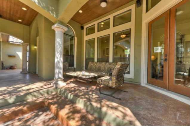 The covered porch is filled with cushioned metal chairs and a matching coffee table.