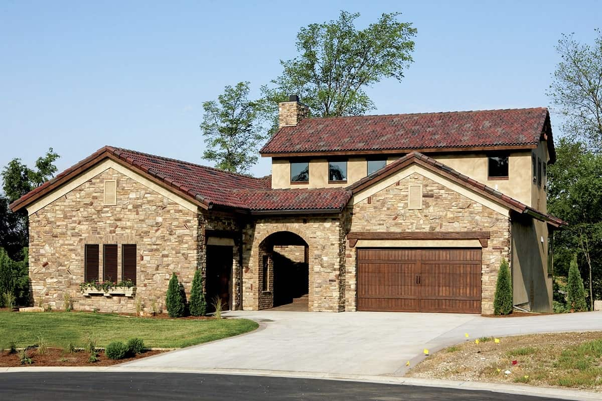 Front exterior view showing the stone and stucco siding, three-car garage, and an arched entryway.