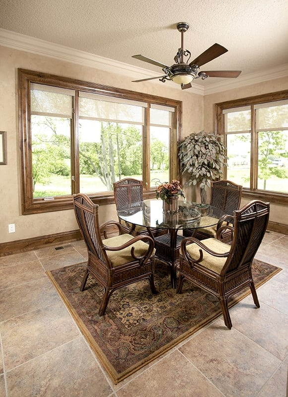 The sunroom has a ceiling fan, a glass top coffee table, and cushioned wicker chairs sitting on a classic area rug.