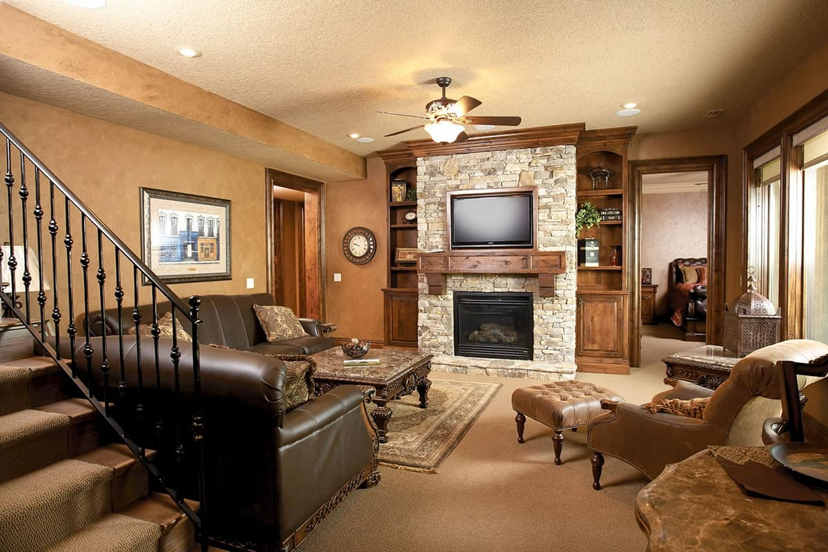 Living room with leather sofas, velvet lounge chair, carved wood coffee table, and a stone fireplace with a TV on top.