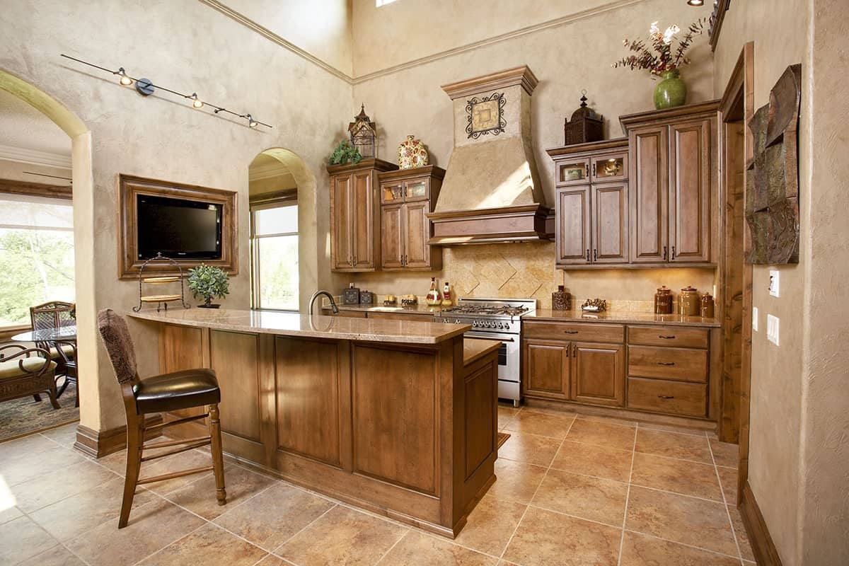 The kitchen is equipped with stainless steel range, wooden cabinetry, and a two-tier island.