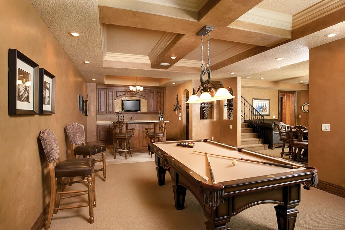 Game room with coffered ceiling, billiard table, a wet bar, and a wine cellar.