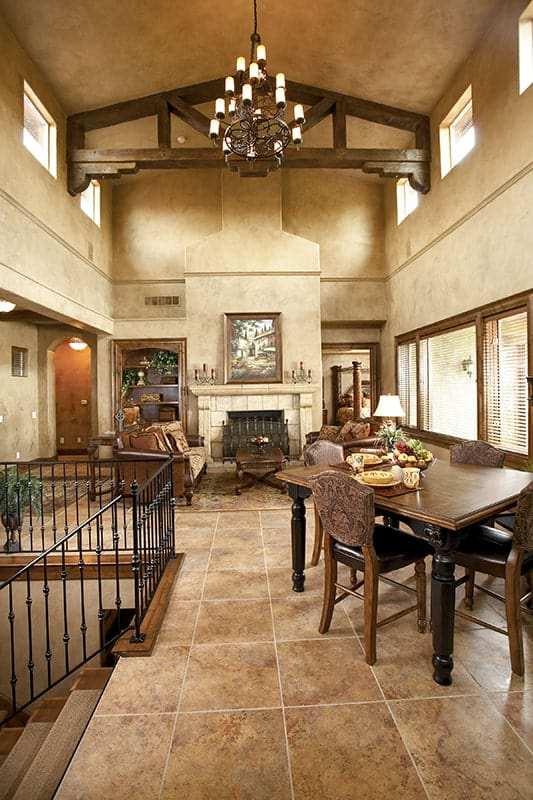 Shared dining and living room with marble tiled flooring and a vaulted ceiling with exposed decorative beams.