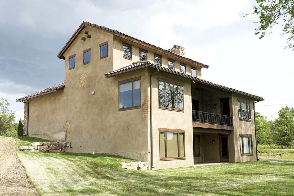 Rear exterior view showing the sloping lot along with covered porch and patio.