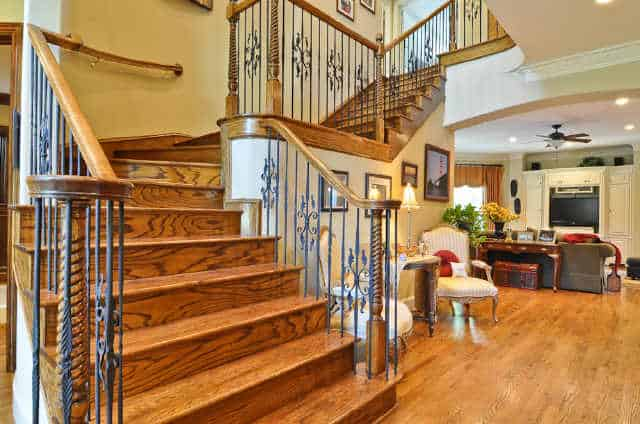 Winding staircase with ornate spindles and wooden steps that match the hardwood flooring.