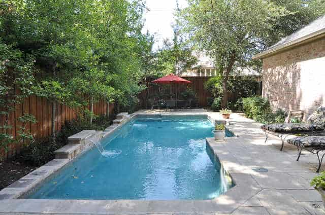 Backyard with a swimming pool surrounded by wooden fence and lush plants.