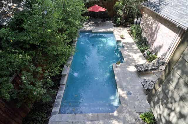 Aerial view of the backyard pool complemented with cushioned loungers.