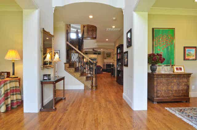 Foyer with wooden console table, gilded mirror, and an open archway leading to the living room.