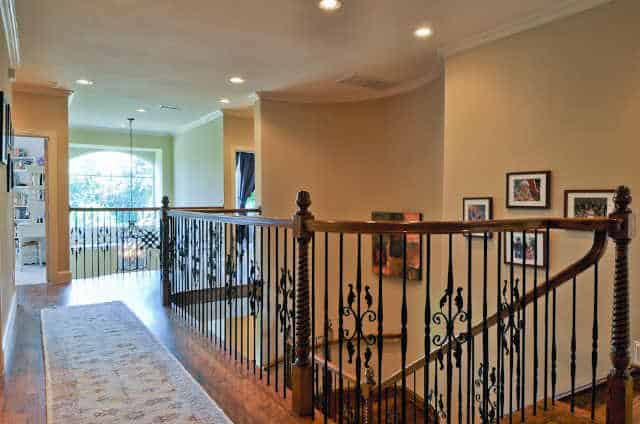 Second-floor balcony with ornate railings and printed runner that lays on the hardwood flooring.