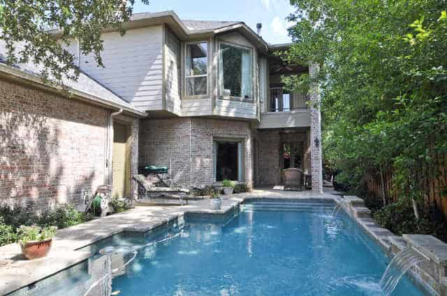 The backyard is filled with a covered patio, a swimming pool, and a double garage.