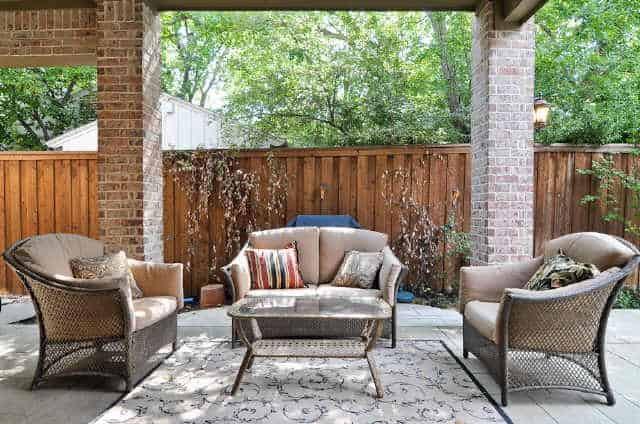 Covered patio with wicker cushioned chairs and a glass top coffee table that sits on a patterned rug.