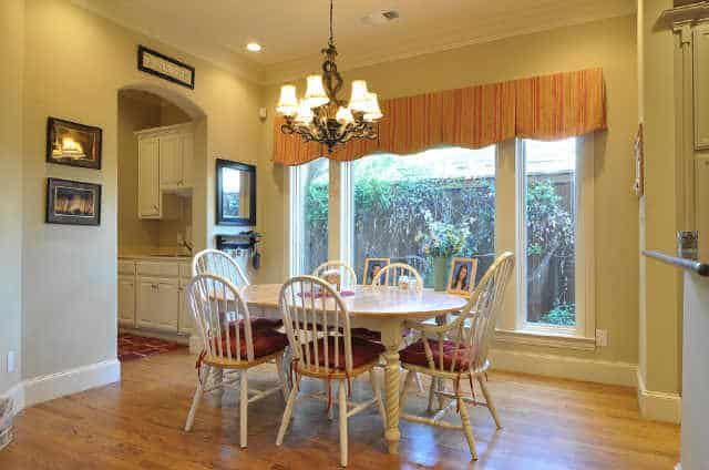 Breakfast nook with round back chairs, an oval dining table, and a classic chandelier.