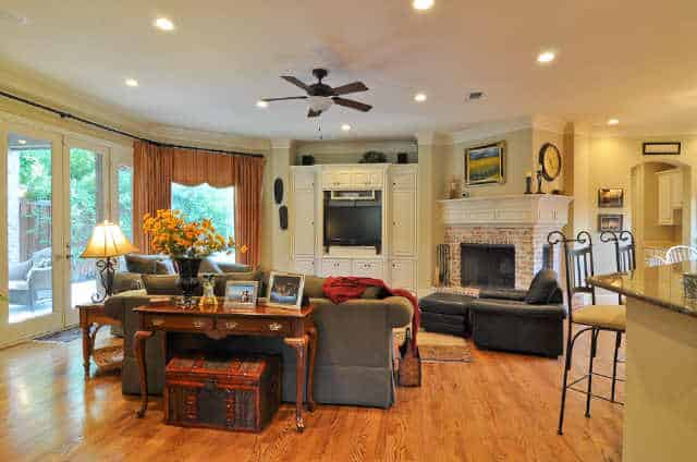 The family room has a corner fireplace, a TV, gray seats, wooden tables, and a french door that leads out to the veranda.