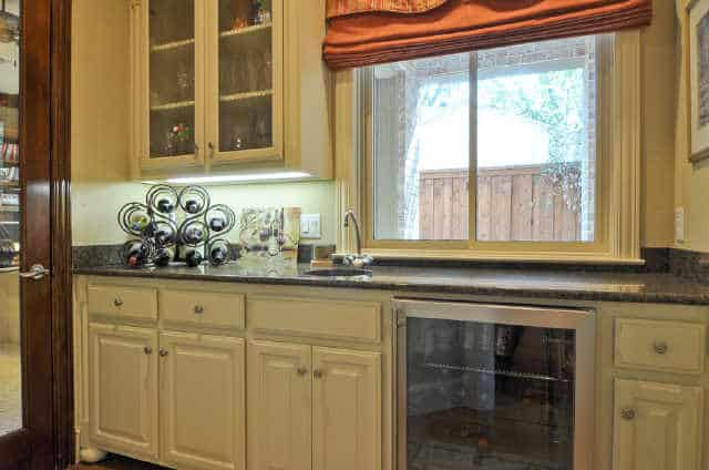 Wet bar with white cabinets, a beverage fridge, and a granite countertop topped with an iron wine rack.