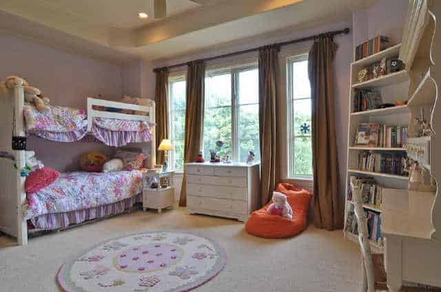Kids' bedroom with white furnishings, a bunk bed, round rug, and glass windows dressed in brown drapes.