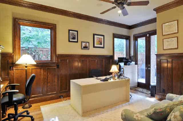 The study has built-in and white center desks, swivel chairs, and yellow walls adorned with framed artworks and wooden wainscoting.