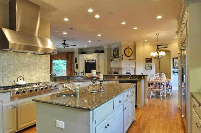 The kitchen is equipped with granite countertops, white cabinets, a two-tier peninsula, and a center island fitted with a round sink.