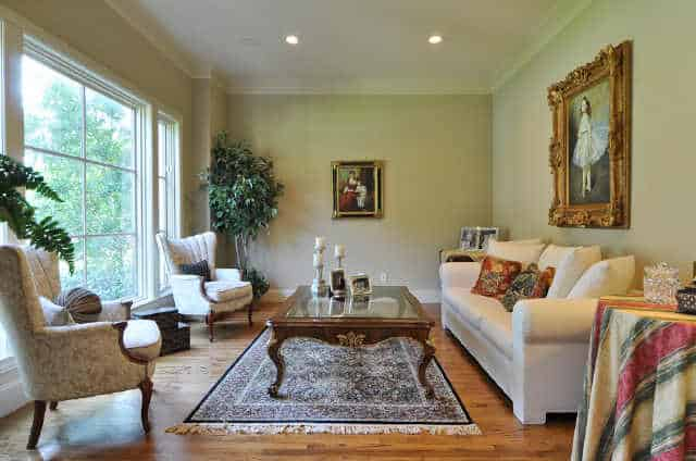 Living room with a white sofa, patterned wingback chairs, and a glass top coffee table over a tasseled area rug.