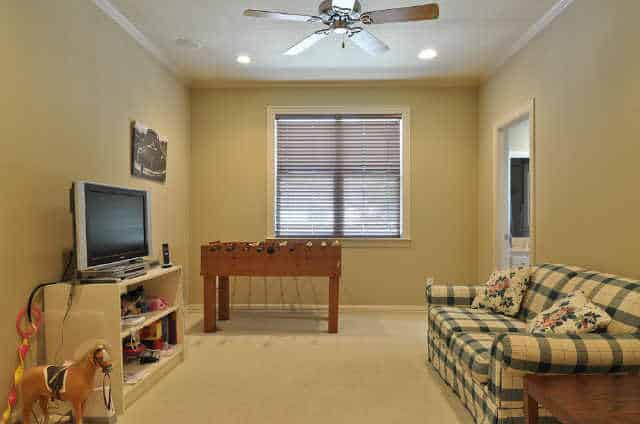 Recreation room with a checkered sofa, game table, a TV, and a ceiling fan.