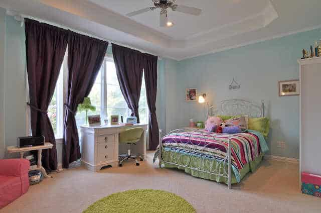 This bedroom has light blue walls, a tray ceiling, a metal bed, a white desk, and a round green rug.