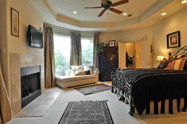 Another bedroom with a tray ceiling, a skirted bed, dark wood dresser, and a white desk paired with a swivel chair.