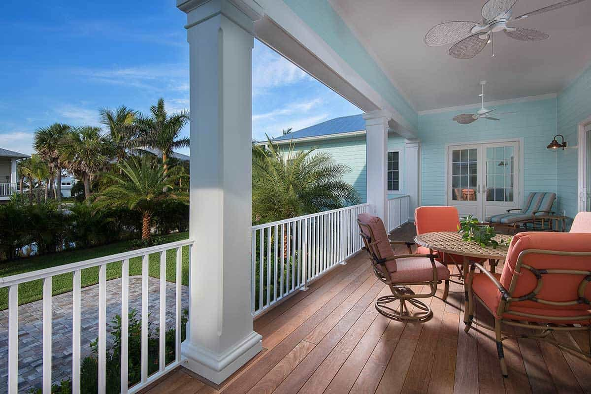 The covered porch is filled with cushioned seats, a round perforated table, and a pair of ceiling fans.