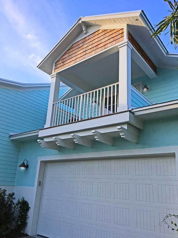Double garage with a white door and a covered balcony on top.