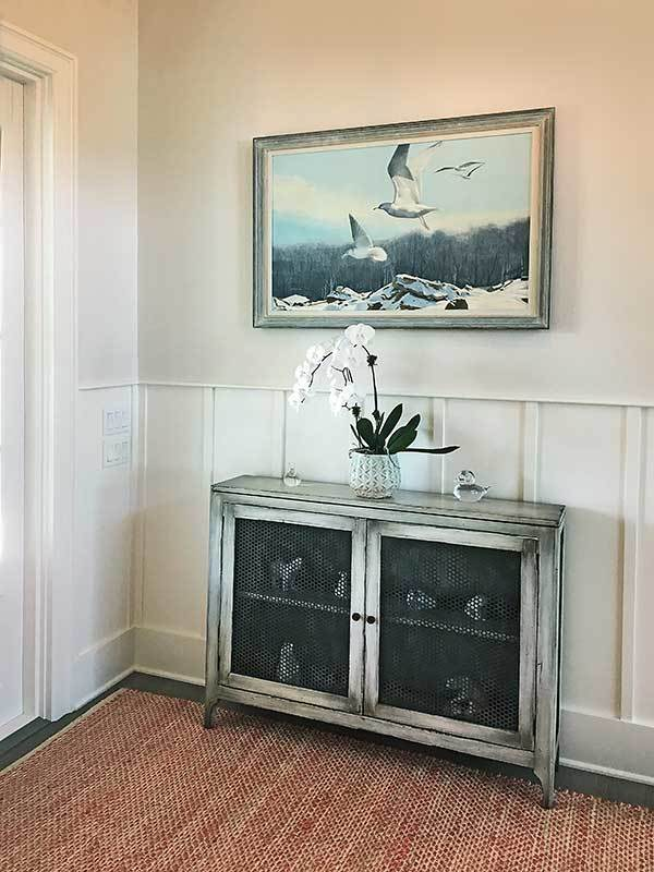 Foyer with a framed painting and a rustic console table topped with a vase and glass figurines.